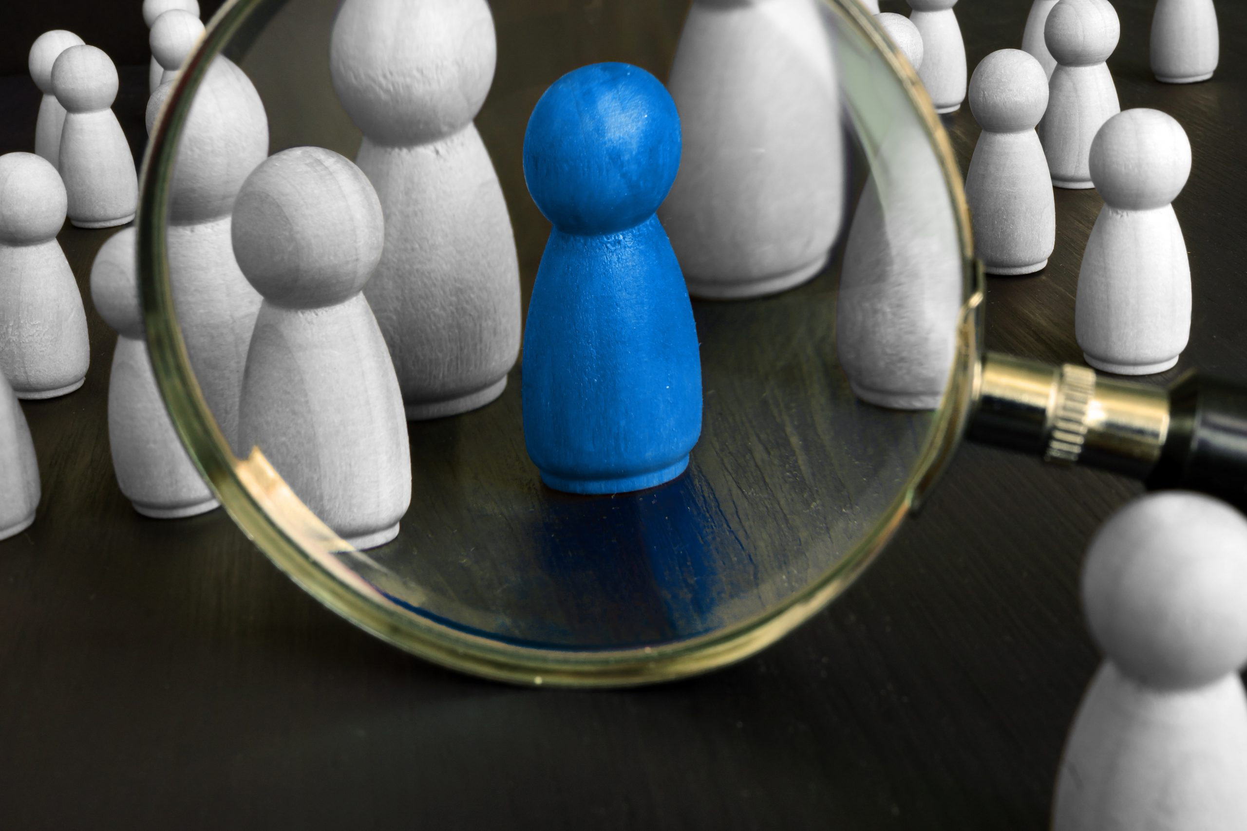 group of wooden pawns with blue focal pawn in a magnifying glass